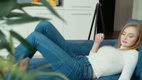 Νέα γυναίκα που χρησιμοποιεί τον υπολογιστή ταμπλετών καθμένος στον καναπέ φιλμ μικρού μήκους