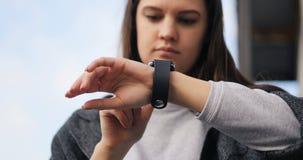 Νέα γυναίκα που χρησιμοποιεί το έξυπνο ρολόι του στην οδό Ο αέρας ταλαντεύεται την τρίχα της Smartwatch, μήλο, χρόνος 4k απόθεμα βίντεο