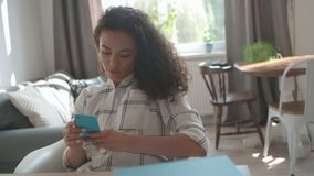 Νέα γυναίκα που χρησιμοποιεί το κινητό τηλέφωνο στο σπίτι απόθεμα βίντεο