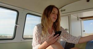 Νέα γυναίκα που χρησιμοποιεί το κινητό τηλέφωνο 4k απόθεμα βίντεο