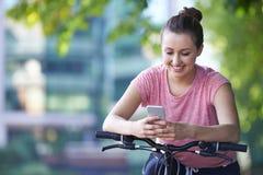Νέα γυναίκα που χρησιμοποιεί το κινητό τηλέφωνο ενώ έξω στο γύρο κύκλων Στοκ φωτογραφίες με δικαίωμα ελεύθερης χρήσης