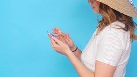 Νέα γυναίκα που χρησιμοποιεί το κινητό τηλέφωνο στο μπλε υπόβαθρο χρώματος απόθεμα βίντεο