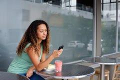 Νέα γυναίκα που χρησιμοποιεί το κινητό τηλέφωνο στο υπαίθριο εστιατόριο καφέδων Στοκ Εικόνες