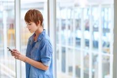 Νέα γυναίκα που χρησιμοποιεί το κινητό τηλέφωνό της στην αρχή με τα παράθυρα Στοκ Εικόνες