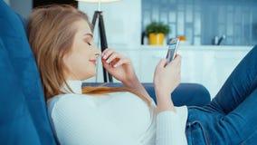 Νέα γυναίκα που χρησιμοποιεί το τηλέφωνο καθμένος στον καναπέ στο σπίτι απόθεμα βίντεο