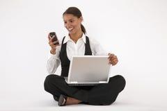 Νέα γυναίκα που χρησιμοποιεί το τηλέφωνο lap-top και κυττάρων Στοκ Φωτογραφίες