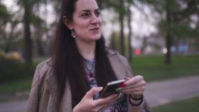 Νέα γυναίκα που χρησιμοποιεί το τηλέφωνό της με το άνθος sakura στο υπόβαθρο - τρόπος ζωής φιλμ μικρού μήκους