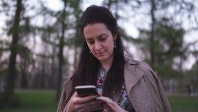 Νέα γυναίκα που χρησιμοποιεί το τηλέφωνό της με το άνθος sakura στο υπόβαθρο - τρόπος ζωής απόθεμα βίντεο