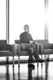 Νέα γυναίκα που χρησιμοποιεί το ψηφιακό PC ταμπλετών του σε ένα σαλόνι αερολιμένων, σύγχρονη αίθουσα αναμονής, με το backlight Στοκ Εικόνες