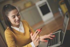 Νέα γυναίκα που χρησιμοποιεί το lap-top και την πιστωτική κάρτα στοκ φωτογραφίες με δικαίωμα ελεύθερης χρήσης