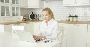 Νέα γυναίκα που χρησιμοποιεί το lap-top στην κουζίνα απόθεμα βίντεο
