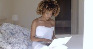Νέα γυναίκα που χρησιμοποιεί το lap-top στο κρεβάτι φιλμ μικρού μήκους