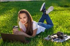 Νέα γυναίκα που χρησιμοποιεί το lap-top στο πάρκο που βρίσκεται στην πράσινη χλόη Έννοια δραστηριότητας ελεύθερου χρόνου Στοκ φωτογραφίες με δικαίωμα ελεύθερης χρήσης