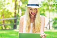 Νέα γυναίκα που χρησιμοποιεί το lap-top της έξω Στοκ φωτογραφία με δικαίωμα ελεύθερης χρήσης
