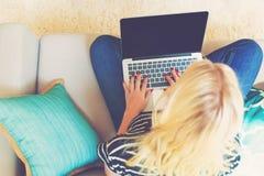 Νέα γυναίκα που χρησιμοποιεί το lap-top της μέσα στον καναπέ της Στοκ Εικόνες