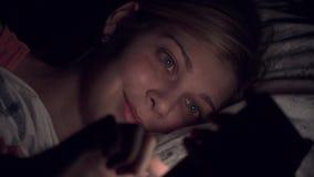 Νέα γυναίκα που χρησιμοποιεί το smartphone στο κρεβάτι απόθεμα βίντεο