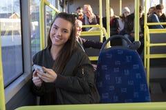 Νέα γυναίκα που χρησιμοποιεί το smartphone της στο λεωφορείο στοκ εικόνες