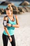 Νέα γυναίκα που χρησιμοποιεί το smartphone armband στην παραλία Στοκ φωτογραφία με δικαίωμα ελεύθερης χρήσης