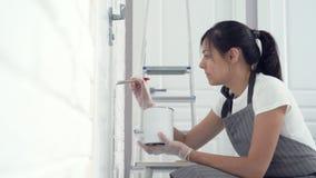Νέα γυναίκα που χρωματίζει το χρώμα τοίχων σε ένα διαμέρισμα ή ένα σπίτι απόθεμα βίντεο