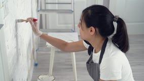 Νέα γυναίκα που χρωματίζει το χρώμα τοίχων σε ένα διαμέρισμα ή ένα σπίτι φιλμ μικρού μήκους