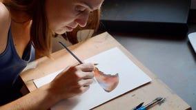 Νέα γυναίκα που χρωματίζει mashroom στο watercolor στο σπίτι στοκ φωτογραφία