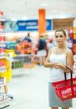 Νέα γυναίκα που ψωνίζει για τα δημητριακά, όγκος σε μια υπεραγορά παντοπωλείων Στοκ Εικόνα