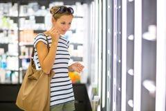 Νέα γυναίκα που ψωνίζει για το σωστό άρωμα Στοκ Φωτογραφίες