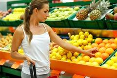 Νέα γυναίκα που ψωνίζει σε μια υπεραγορά στο τμήμα φρούτων Στοκ Φωτογραφία