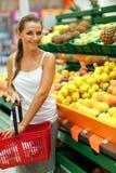Νέα γυναίκα που ψωνίζει σε μια υπεραγορά στο τμήμα φρούτων Στοκ Εικόνα
