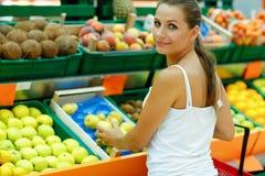 Νέα γυναίκα που ψωνίζει σε μια υπεραγορά στο τμήμα φρούτων Στοκ Φωτογραφίες