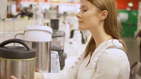 Νέα γυναίκα που ψωνίζει στις συσκευές κουζινών αγοράς καταστημάτων Παίρνοντας τα thermos, που επιλέγουν την κατσαρόλα απόθεμα βίντεο