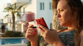 Νέα γυναίκα που ψωνίζει on-line με την πιστωτική κάρτα και το κόκκινο smartphone φιλμ μικρού μήκους
