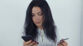 Νέα γυναίκα που ψωνίζει on-line με την πιστωτική κάρτα και το smartphone φιλμ μικρού μήκους