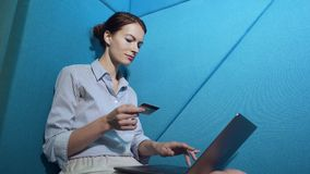 Νέα γυναίκα που ψωνίζει on-line με την πιστωτική κάρτα στο lap-top απόθεμα βίντεο