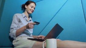 Νέα γυναίκα που ψωνίζει on-line με την πιστωτική κάρτα στο lap-top φιλμ μικρού μήκους