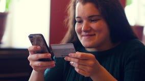 Νέα γυναίκα που ψωνίζει on-line χρησιμοποιώντας μια πιστωτική κάρτα που χρησιμοποιεί ένα smartphone απόθεμα βίντεο