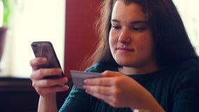 Νέα γυναίκα που ψωνίζει on-line χρησιμοποιώντας μια πιστωτική κάρτα που χρησιμοποιεί ένα smartphone φιλμ μικρού μήκους
