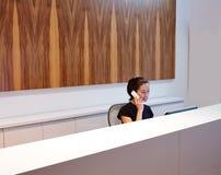 Νέα γυναίκα ρεσεψιονίστ Brunette στο γραφείο Στοκ φωτογραφίες με δικαίωμα ελεύθερης χρήσης
