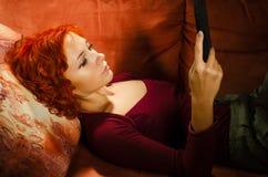 Νέα γυναίκα σε έναν καναπέ με το PC ταμπλετών στοκ εικόνες