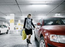 Νέα γυναίκα σε έναν χώρο στάθμευσης κοντά σε ένα αυτοκίνητο Κορίτσι μετά από να ψωνίσει στοκ εικόνα