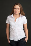 Νέα γυναίκα σε ένα άσπρο πουκάμισο στο γκρίζο κλίμα Στοκ Εικόνες