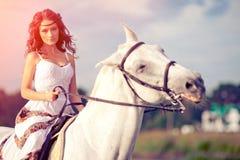 Νέα γυναίκα σε ένα άλογο Αναβάτης πλατών αλόγου, άλογο οδήγησης γυναικών στο β Στοκ Εικόνες