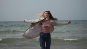 Νέα γυναίκα σε ένα αδιάβροχο που χορεύει στην παραλία της θάλασσας, που περπατά κατά μήκος της ακτής απόθεμα βίντεο
