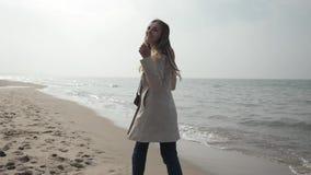 Νέα γυναίκα σε ένα αδιάβροχο που χορεύει στην παραλία της θάλασσας, που περπατά κατά μήκος της ακτής φιλμ μικρού μήκους