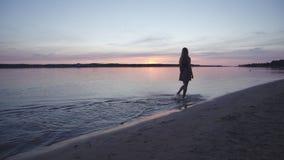 Νέα γυναίκα σε ένα κοντό θερινό φόρεμα που περπατά και που καταβρέχει κατά μήκος της παραλίας που απολαμβάνει το υπόβαθρο ζωής κα απόθεμα βίντεο
