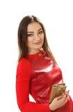 Νέα γυναίκα σε ένα κόκκινο φόρεμα με ένα πορτοφόλι Στοκ Φωτογραφίες