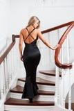 Νέα γυναίκα σε ένα μακρύ μαύρο φόρεμα στοκ φωτογραφία