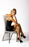 Νέα γυναίκα σε ένα μαύρο φόρεμα που θέτει τη συνεδρίαση σε μια καρέκλα Στοκ Εικόνες
