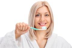 Νέα γυναίκα σε ένα μπουρνούζι που κρατά μια οδοντόβουρτσα Στοκ Εικόνα