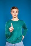Νέα γυναίκα σε ένα μπλε υπόβαθρο που παρουσιάζει σημάδια Στοκ φωτογραφία με δικαίωμα ελεύθερης χρήσης
